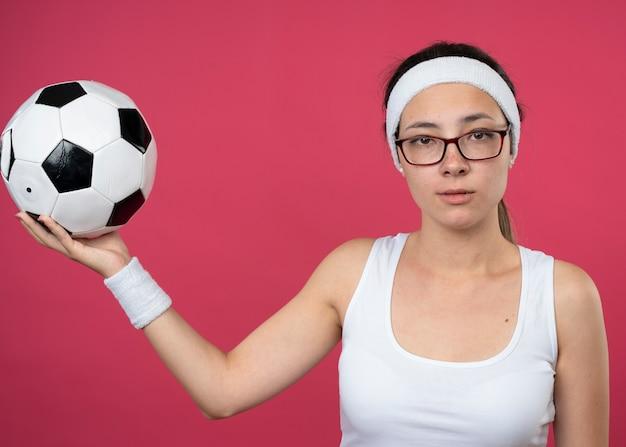 Zekere jonge sportieve vrouw in optische glazen die hoofdband en polsbandjes dragen die bal houden die op roze muur wordt geïsoleerd