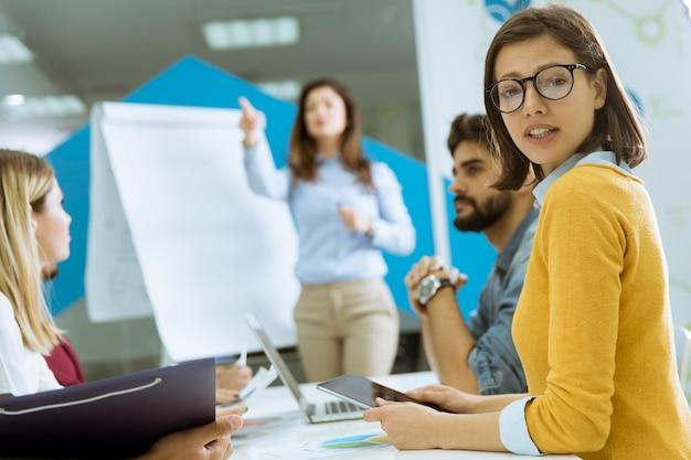 Zekere jonge teamleider die een presentatie geeft aan een groep jonge collega's terwijl ze zitten gegroepeerd op de flip-over in het kantoor