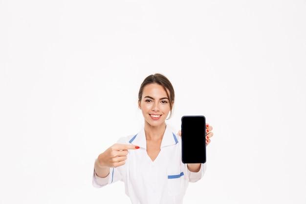 Zekere jonge vrouw arts die eenvormige status draagt die over witte muur wordt geïsoleerd, die leeg scherm mobiele telefoon toont