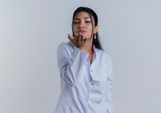 Zekere jonge vrouwelijke arts die medische mantel draagt die verzendende geïsoleerde klapkus kijkt
