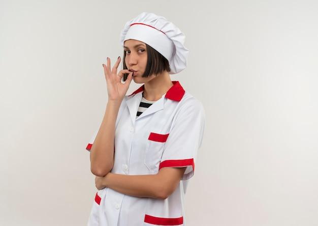 Zekere jonge vrouwelijke kok in eenvormige chef-kok die smakelijk gebaar doet dat op wit met exemplaarruimte wordt geïsoleerd