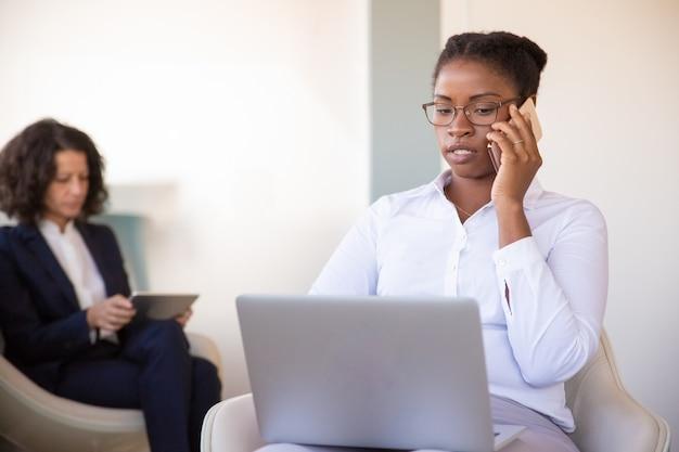 Zekere jonge vrouwelijke manager die cellphone uitnodigt