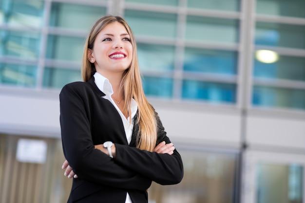 Zekere jonge vrouwelijke manager openlucht in het moderne stedelijke plaatsen