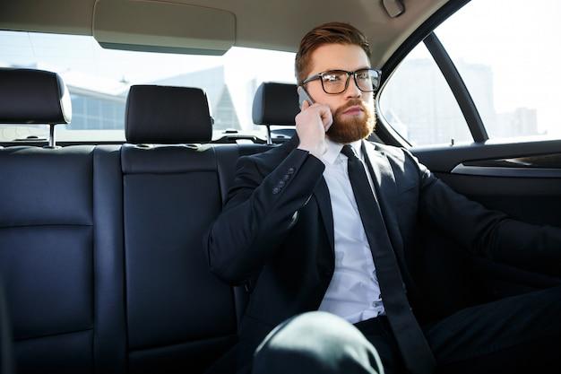 Zekere jonge zakenman die op mobiele telefoon spreekt