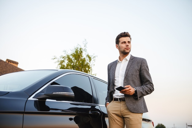 Zekere jonge zakenman in kostuum dat zich bij zijn auto bevindt
