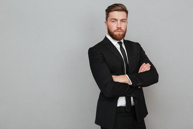Zekere jonge zakenman in kostuum die zich met gevouwen wapens bevinden