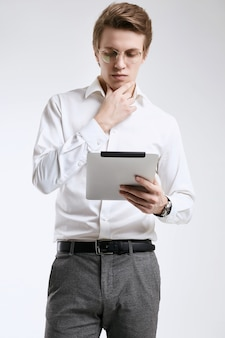 Zekere jonge zakenman in overhemd die aan digitale tablet werken