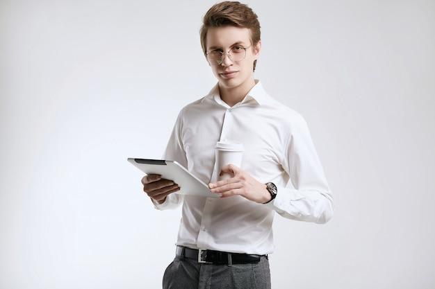 Zekere jonge zakenman in overhemd met kop van koffie en tablet