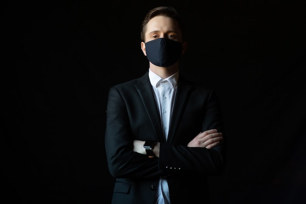 Zekere jonge zakenman met gekruiste wapens die een beschermend medisch masker dragen