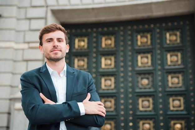 Zekere jonge zakenman met zijn gekruiste wapens status voor gesloten deur
