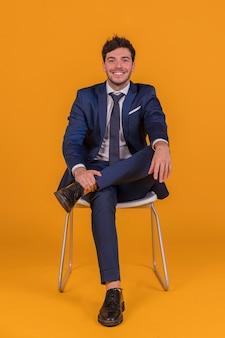 Zekere jonge zakenmanzitting op witte stoel tegen een oranje achtergrond