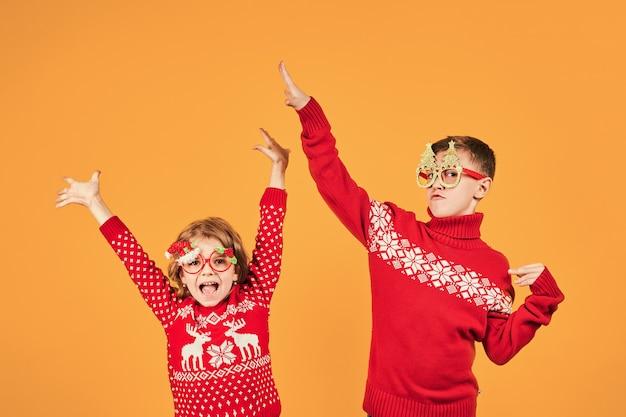 Zekere kinderen die in warme rode kerstmissweaters en verfraaide glazen camera op gele achtergrond bekijken