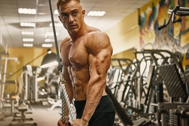 Zekere knappe atletische bodybuilder training triceps pushdown in gymnastiek