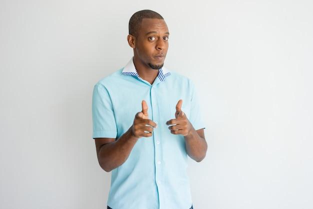 Zekere koele afrikaanse kerel die op u met vingerkanonnen richt.