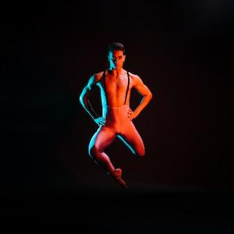 Zekere mannelijke balletdanser die in schijnwerper presteert