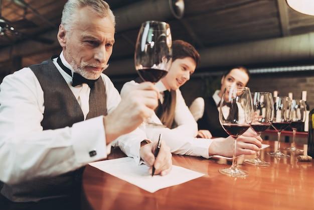 Zekere meer sommelier proevende wijn in restaurant.