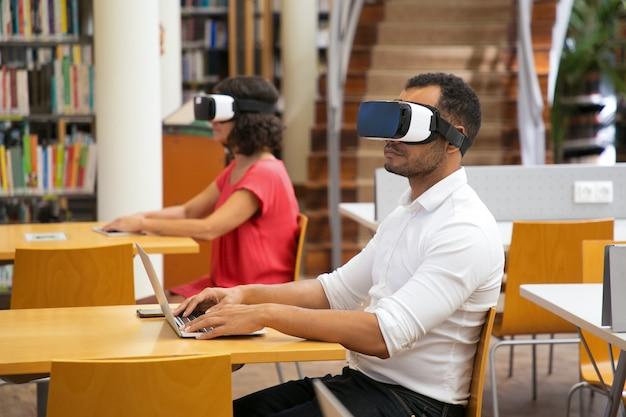 Zekere mens die op laptop typen terwijl het zitten in vr-hoofdtelefoon