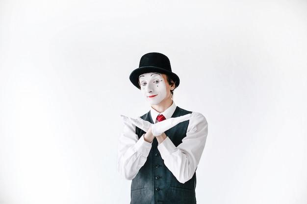 Zekere mime in zwarte hoed houdt zijn hand zoals vogelvleugels