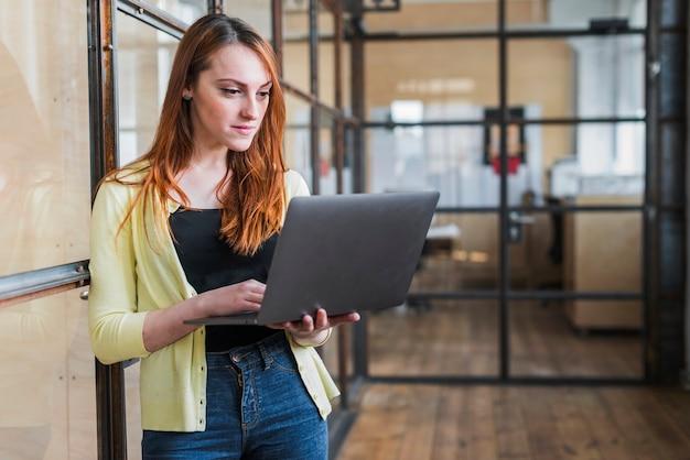 Zekere onderneemster die laptop met behulp van op het werk