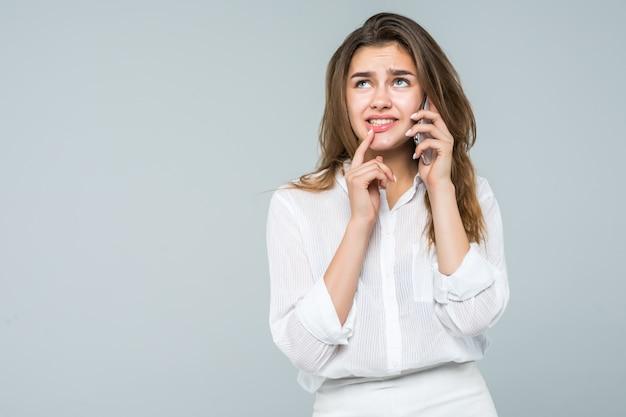 Zekere onderneemster die op de mobiele celtelefoon spreekt die op wit wordt geïsoleerd