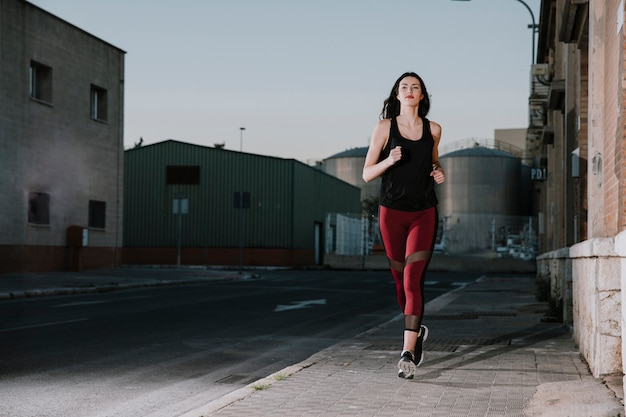 Zekere sportvrouw die op straat loopt