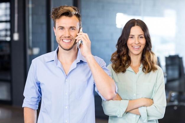 Zekere stafmedewerker die op telefoon met vrouwelijke collega spreken die zich naast in bureau bevinden
