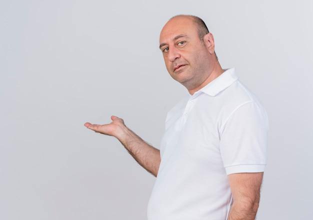 Zekere toevallige volwassen zakenman die zich in profielmening bevindt die camera bekijkt en met hand aan kant richt die op witte achtergrond met exemplaarruimte wordt geïsoleerd