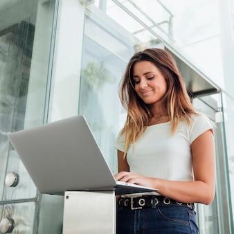 Zekere vrouw die in jeans haar laptop doorbladert