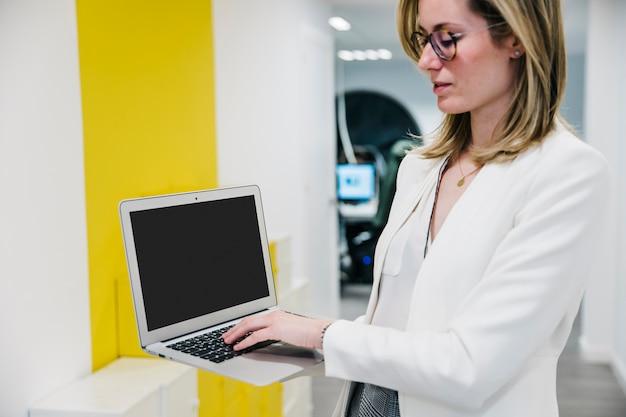 Zekere vrouw die laptop in bureau met behulp van