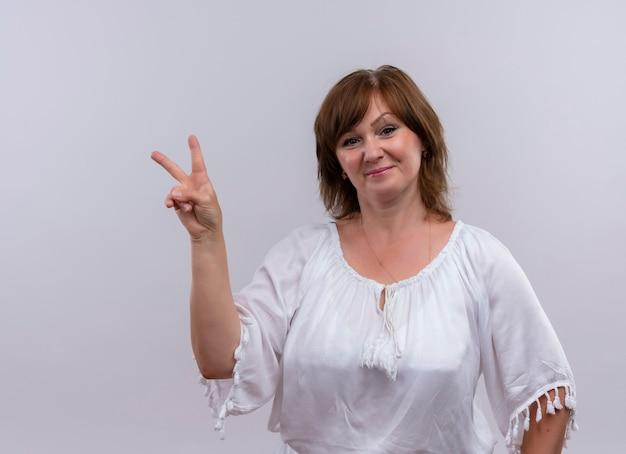 Zekere vrouw die op middelbare leeftijd vredesteken op geïsoleerde witte muur toont