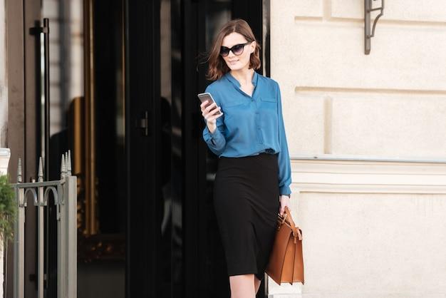 Zekere vrouw in zonnebril die mobiele telefoon met behulp van