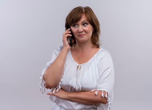 Zekere vrouw op middelbare leeftijd die mobiele telefoon aan oor op geïsoleerde witte muur houdt