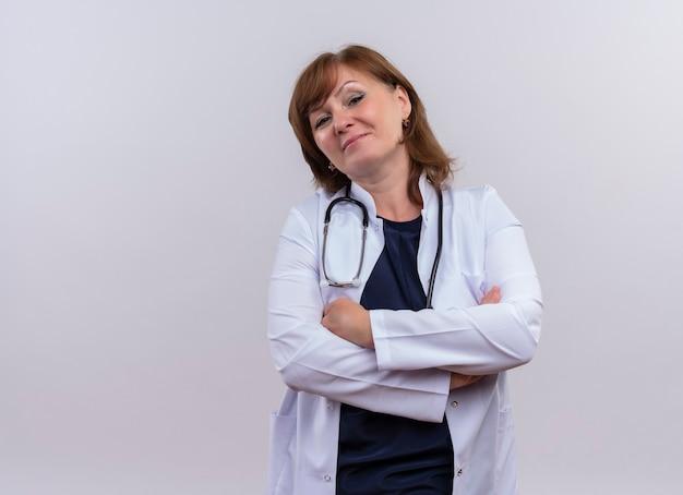 Zekere vrouw van middelbare leeftijd arts die medische mantel en stethoscoop draagt die zich met gesloten houding op geïsoleerde witte muur met exemplaarruimte bevindt