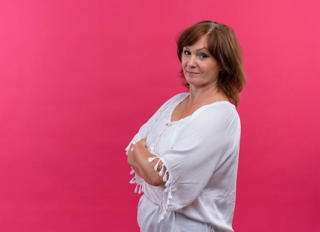 Zekere vrouw van middelbare leeftijd die zich met gesloten houding op geïsoleerde roze muur bevindt
