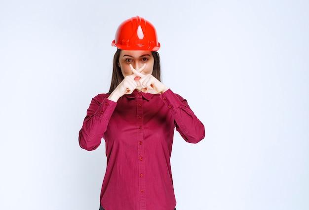 Zekere vrouwelijke architect in rode harde helm die eindeteken toont.