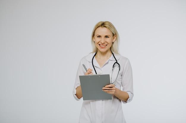 Zekere vrouwelijke arts in witte medische laag en stethoscoop die kalm op klembord met geduldige medische geschiedenis kijken