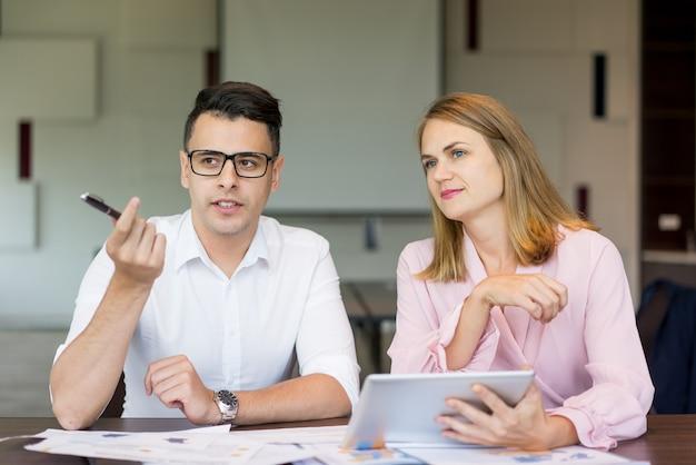 Zekere zakenman die aan vrouwelijke collega bij briefing spreekt.
