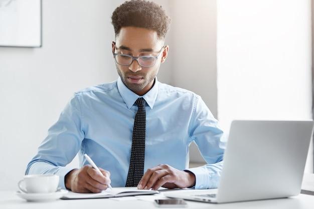Zekere zakenman die aan zijn laptop werkt