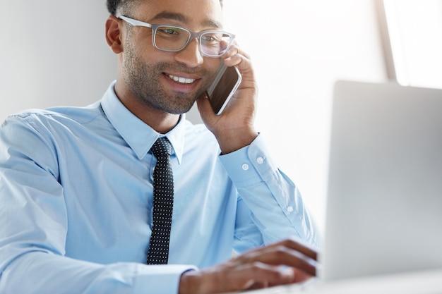 Zekere zakenman die aan zijn laptop werkt Gratis Foto