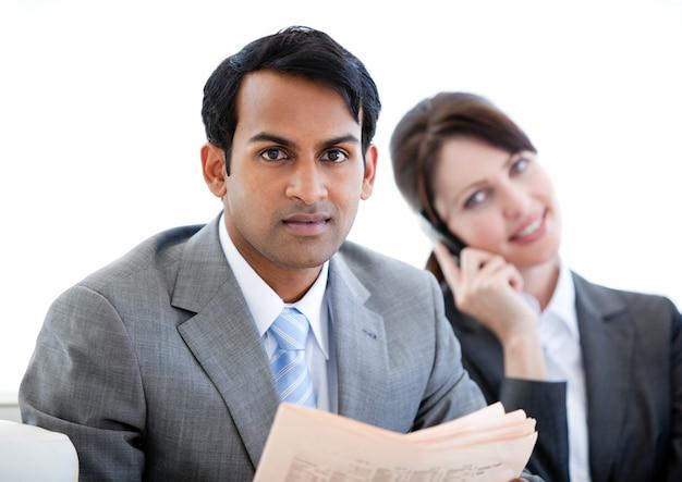 Zekere zakenman die een krant in een wachtkamer leest