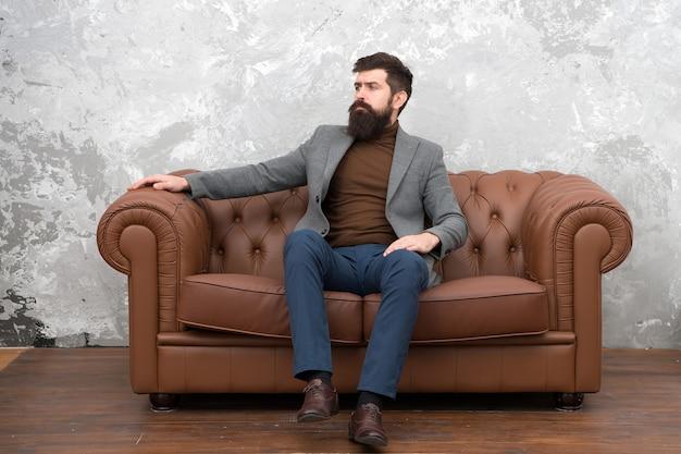 Zelf authentiek zijn. man van zaken. elegante zakenman ontspannen op de bank. zelfverzekerde businesscoach. bebaarde man in casual zakelijke kleding.