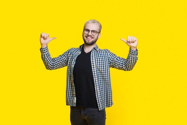 Zelf trotse man gebaart naar zichzelf glimlachend op een gele muur door een bril met een baard be