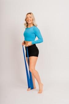 Zelfbepaalde bodybuilder doet oefeningen met elastiek, werkt op handen en benen. sportconcept.