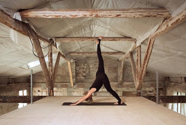 Zelfbouw. een jonge atletische vrouw oefent yoga op een verlaten bouwgebouw. geestelijke en lichamelijke gezondheid. concept van een gezonde levensstijl, sport, activiteit, gewichtsverlies, concentratie.