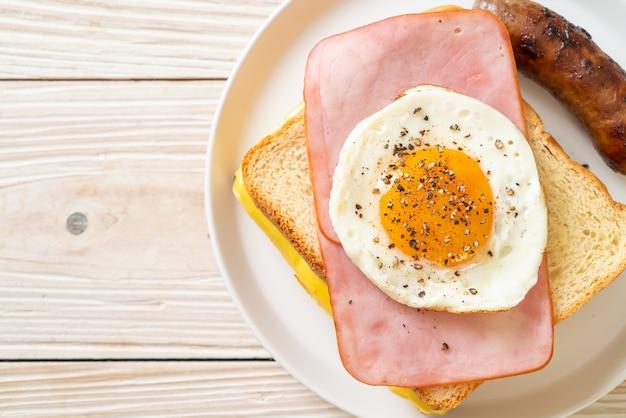 Zelfgebakken brood geroosterde kaas belegd ham en gebakken ei met varkensworst als ontbijt