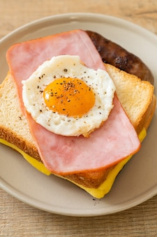 Zelfgebakken brood geroosterde kaas belegde ham en gebakken ei met varkensworst als ontbijt