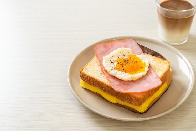 Zelfgebakken brood geroosterde kaas belegde ham en gebakken ei met varkensworst en koffie als ontbijt