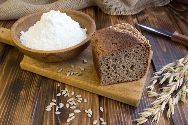 Zelfgebakken brood gesneden op de snijplank op de bruine houten achtergrond