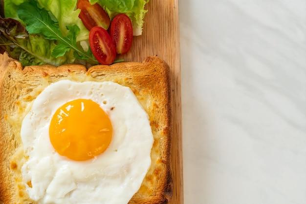 Zelfgebakken brood getoast met kaas en gebakken ei erop met groentesalade als ontbijt