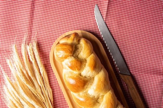 Zelfgebakken brood, gevlochten brood op hout en een rood en wit geruit tafelkleed, een mes en een tak van tarwe, bovenaanzicht.